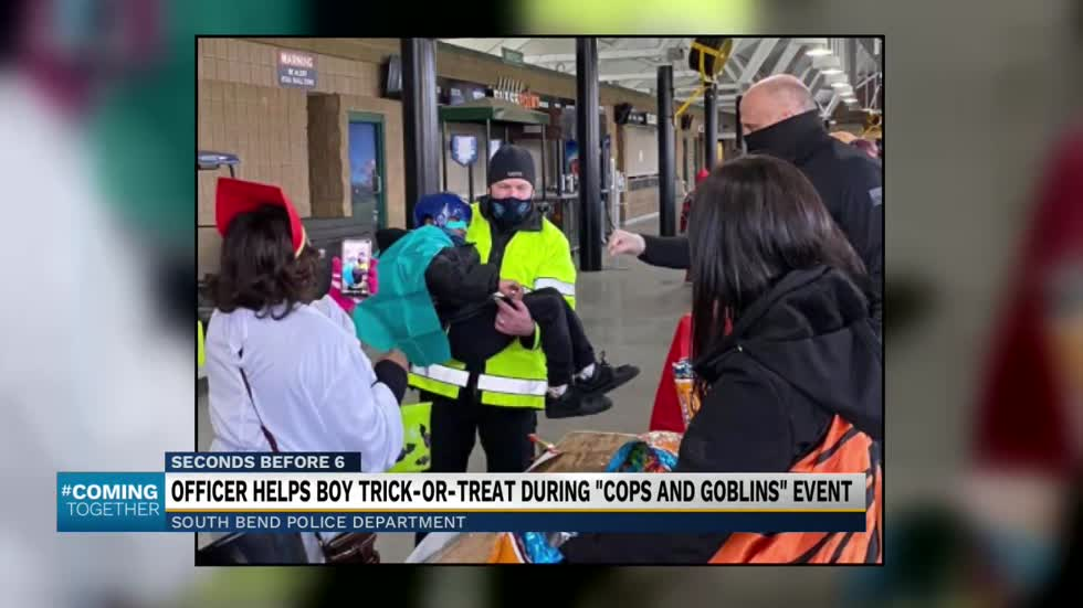 Police officer carries kid around trick-or-treating event in...